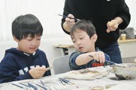 「マイストーン」や木の表札に色付けする子どもたち