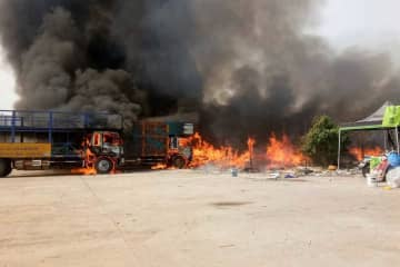 Vehicles burn in the parking lot at K Transport Co in Samut Prakan's Muang district on Sunday afternoon. Six six-wheel trucks and a motorcycle were destroyed. (Photo by Sutthiwit Chayutworakan)