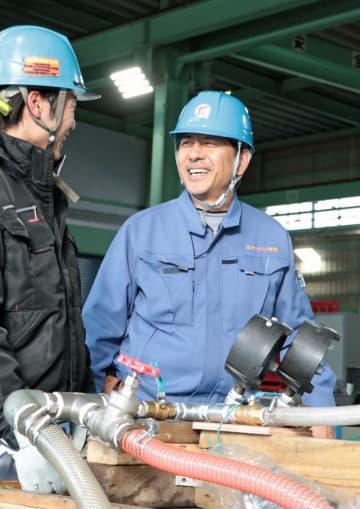 現場で従業員と話をする徳重さん(右)=佐世保市、東洋トラスト特機