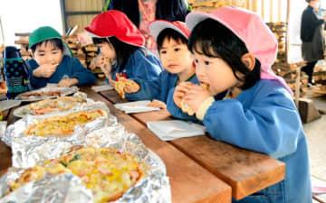 自分たちで作ったピザをほおばる長月保育所の園児ら