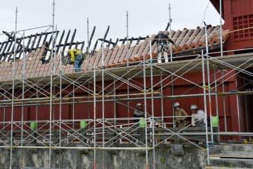 首里城の奉神門の屋根などを撤去するため、足場を設置する作業員=10日午後、那覇市