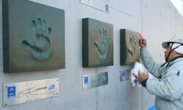 左からウルグアイ、フィジー、フランス各主将の手形モニュメント=10日、大分市の豊後企画大分駄原球技場