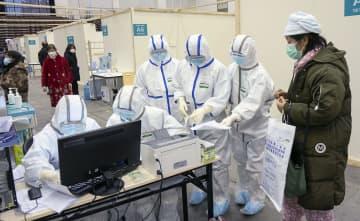 中国・武漢市内のホールに臨時に設置された病院で、新型肺炎患者に対応する防護服姿の医療従事者ら=10日(新華社=共同)