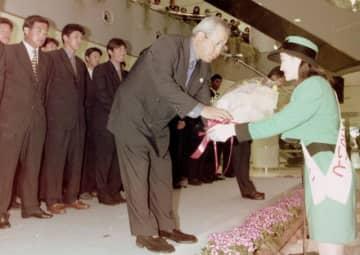 西都市での春季キャンプのため空路本県入りし、歓迎の花束を受け取るヤクルト・野村克也監督=1998年2月23日、宮崎市・宮崎空港
