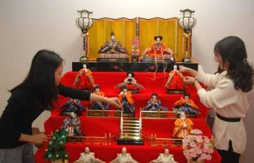 【ひな人形を飾るベトナム国籍の女性ら=亀山市東町の市市民協働センターで】