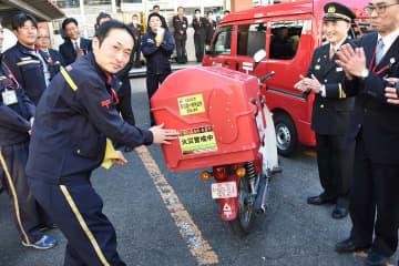 「火災警戒中」のステッカーをバイクに貼る横浜南郵便局員=横浜南郵便局