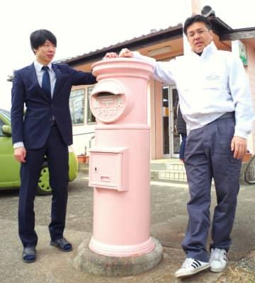 新たにお目見えしたピンクの円柱型ポストと佐瀬局長(左)、平山社長=東金市