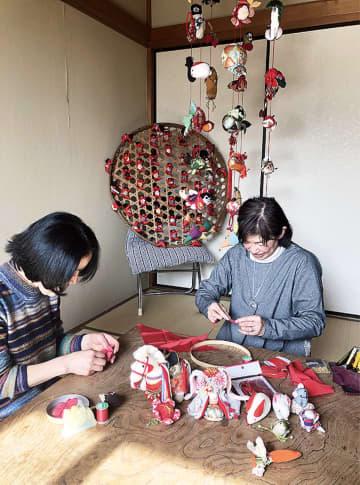 回顧展に向けて作品づくりをする高島代表(写真右)