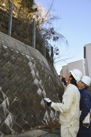 土砂災害警戒区域に指定されている神奈川県逗子市の市道脇の斜面を点検する市職員=13日午後