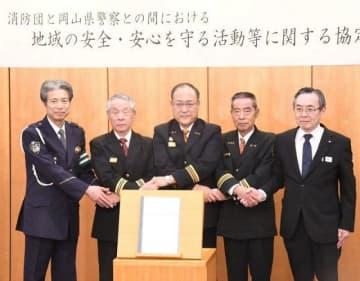 協定書に調印後、握手を交わす県警幹部と消防団長