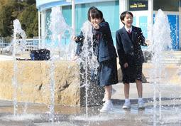 陽気の下、噴水の水に触れてはしゃぐ中学生ら=13日午後、神戸市中央区波止場町