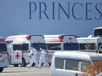 クルーズ船の近くには救急車が並び、新たに感染が確認された人たちの搬送が続いた=13日午後1時25分ごろ、横浜港・大黒ふ頭