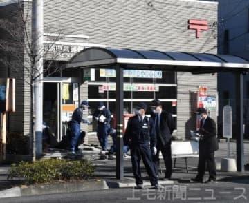 被害に遭った群馬中泉郵便局の入り口を調べる捜査員=13日午後2時55分ごろ、高崎市中泉町