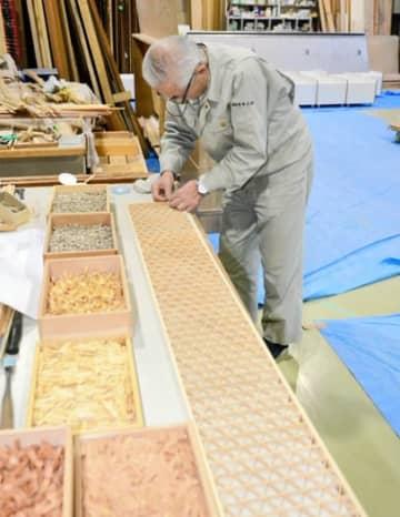 緻密な木の細工を完成させる関係者=伊達クラフトデザインセンター