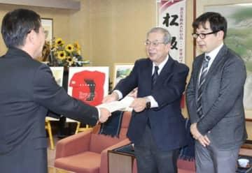 【伊佐地委員長(中央)から提言書を受け取る竹上市長(左)=松阪市役所で】
