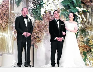 Siritaj Rojanapruk, chief executive officer of Com-Link and father of the groom, with the bride and groom Apichit Jinakul