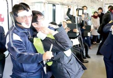乗客にナイフを突き付ける犯人役=7日、吉川市美南のJR吉川美南駅