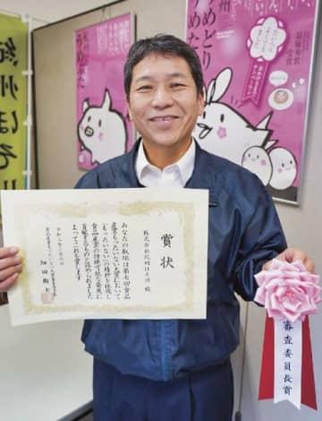 審査委員会委員長賞の賞状を手にする細川庄三社長