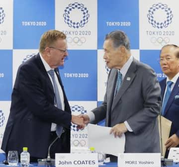 記者会見を終えて握手するIOCのコーツ調整委員長(左)と大会組織委の森喜朗会長=14日午後、東京都中央区