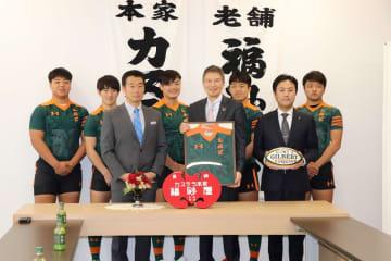 東福岡高ラグビーフットボール部からジャージーとボールを贈られた殿村副社長(右から4人目)=福岡市中央区、福砂屋赤坂店