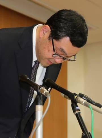 記者会見で頭を下げて謝罪する鈴木本部長