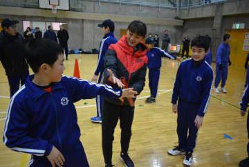 台湾の高校生トップ選手(中央)からバトンの受け渡しを学ぶ児童