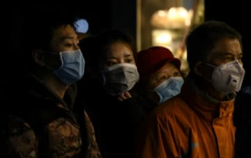People wearing protective facemasks queue for food in Shanghai.