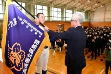 阿部校長から選抜旗を受ける岩間主将(左)
