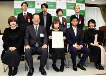 記念撮影する大賞の高野ユタさん(前列中央)はじめ受賞者と審査員ら=14日午後、松山市役所