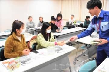 備蓄用食品のアルファ化米を受け取る外国人
