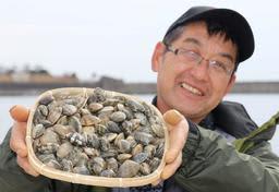 室津港沖の天然アサリから養殖したアサリを持つ磯部公一さん=姫路市網干区興浜