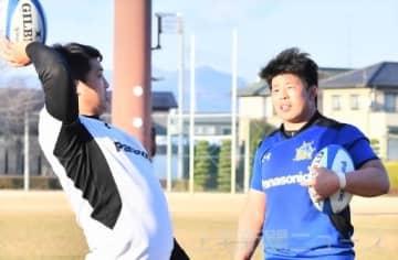 坂手主将(左)からラインアウト時の球の投げ入れ方の指導を受ける島根=13日、太田市龍舞町