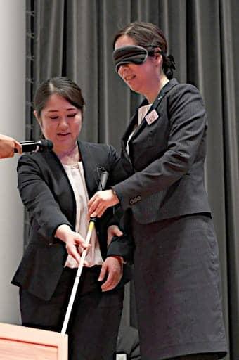 視覚障害がある人と列車に乗る方法を体験する社員ら=14日、大阪市北区の大阪工業大常翔ホール