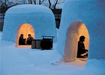 撮影会で、雪室の中で火鉢を囲む子どもたち。今年のかまくらは山間部から運んだ雪で作られた=14日午後5時30分ごろ、横手市雄物川町