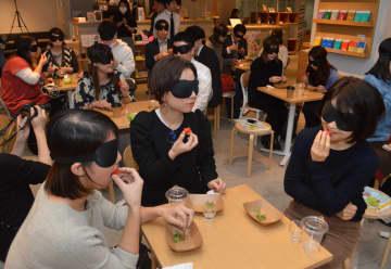 アイマスクをした状態で大田原市産イチゴを味わう参加者たち=14日夜、東京・渋谷