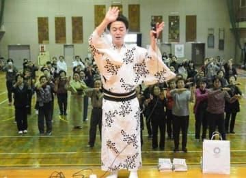 鳳蝶美成さん(手前)の指導を受け、「東京五輪音頭2020」の振り付けを覚える講習会の参加者=熊本市西区