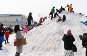 十日町雪まつり会場の雪山で遊ぶ子どもたち=15日