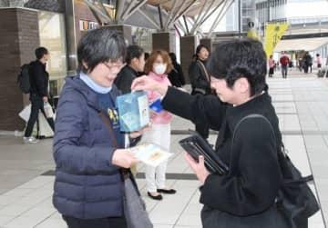 小児がんへの理解と支援を呼び掛ける阿部さん(左)ら=JR岡山駅