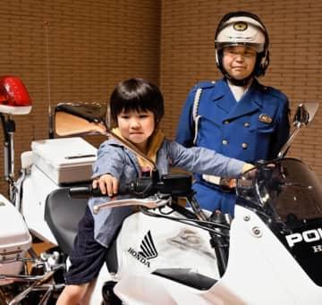 白バイに体験乗車し、笑顔を見せる子ども