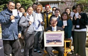 昔のクラスの思い出の写真を持つ與那嶺剛さん(前列中央)と、與那嶺さんから届いた年賀状を手にする元2年6組のメンバー=6日、うるま市・あげな中学校