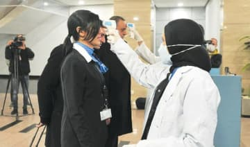 Egyptian Quarantine Authority employees prepare to scan body temperatures of incoming travelers at Cairo International Airport.
