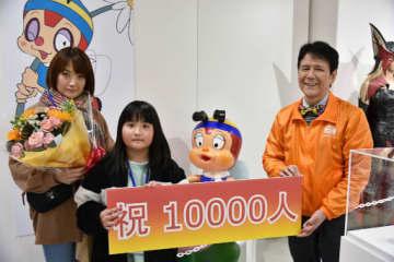 入館1万人目となった治郎丸琴さん(左から2人目)=15日、倉吉市鍛冶町1丁目の円形劇場くらよしフィギュアミュージアム