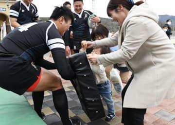 大阪府警ラグビー部員(左)とタックル体験する家族連れ=15日、兵庫県宝塚市の宝塚北サービスエリア