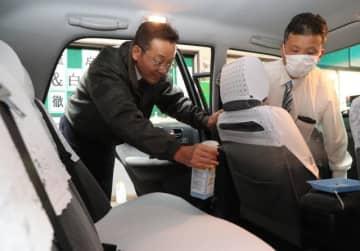 新型コロナウイルス感染防止のため、車内を消毒するタクシー会社社員=15日午後、宮崎市小松