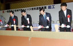 工事の安全と早期開通を願い、くわ入れを行う関係者ら=16日午後、神戸市西区平野町宮前