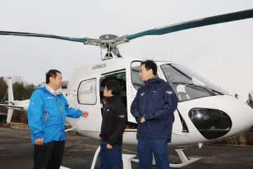 ピースウィンズ・ジャパンのヘリの前でプロジェクトについて話す大西代表理事(左)と稲葉さん(中)たち