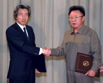 2002年9月、平壌宣言の署名を終え、握手する小泉首相(左)と金正日総書記=平壌の百花園迎賓館(共同)