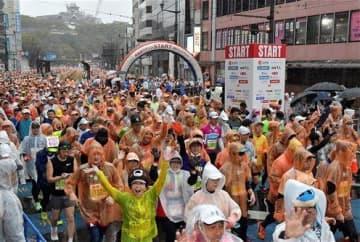 雨の中、熊本城をバックにスタートするフルマラソンのランナー=16日午前9時10分ごろ、熊本市中央区の通町筋電停前(後藤仁孝)