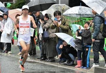 雨が降る中、傘を差して設楽悠太(ホンダ)に声援を送る沿道の人たち=16日午前、熊本市中央区(池田祐介)