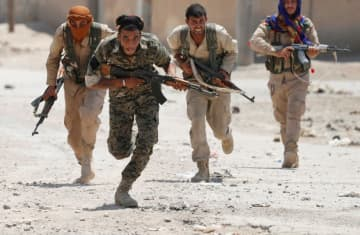 Kurdish fighters from the People's Protection Units (YPG) run from ISIS gunmen in Raqqa, Syria, July 3, 2017. (photo credit: REUTERS/GORAN TOMASEVIC/FILE PHOTO)